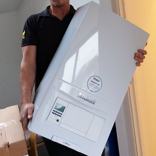 Thumbnail photo of a gas engineer carrying a new Vaillant boiler as part of a boiler installation.
